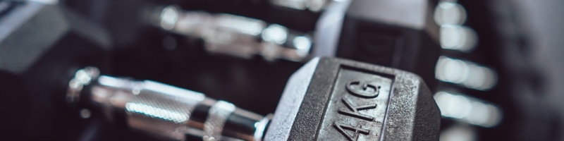 Close up many metal dumbbells on rack in sport fitness center.Highlight.